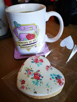 Iced shortbread biscuit with a mug of tea with a picture of a sewing machine saying sewing is my superpower placed on a coffee table